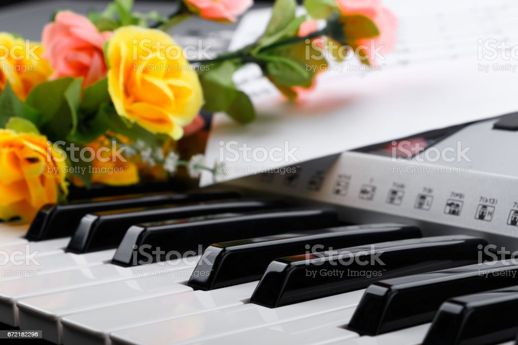 Fragment of electronic synthesizer keyboard with flowers and music notes sheets stock photo