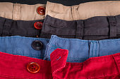 Fragment of four cotton twill pants red, blue, black, beige