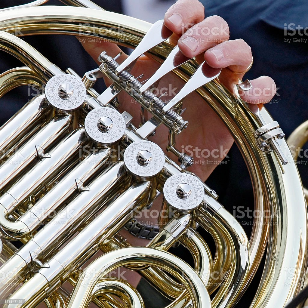Fragment of French horn being played in orchestra, shallow DOF royalty-free stock photo