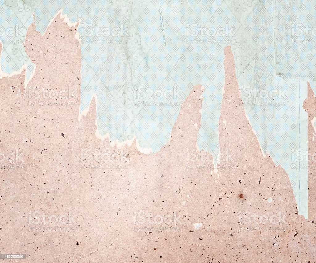Fragment of old destroyed wall with wallpaper in abandoned house stock photo