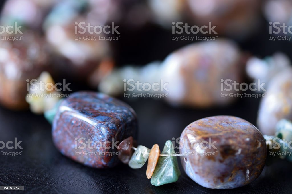 Fragment of stone necklace on a dark surface stock photo