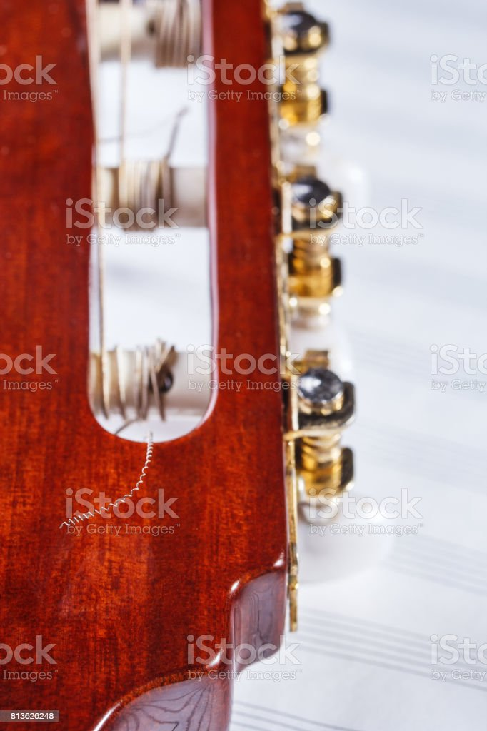 Fragment of the head of the fretboard of a classical guitar on a background of a musical note stock photo