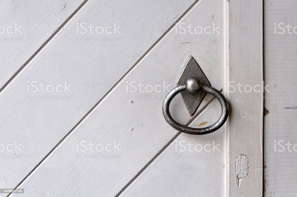 Fragment of white old wooden door with metal vintage ring. stock photo
