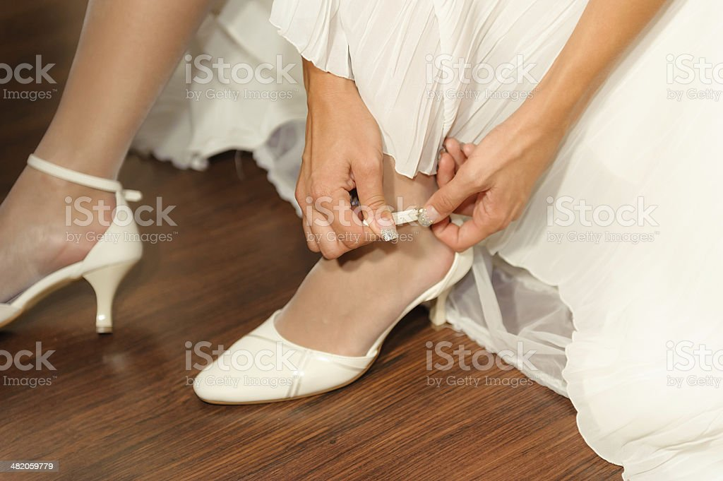 Fragment of woman's arm and hands fastening white wedding shoes. stock photo