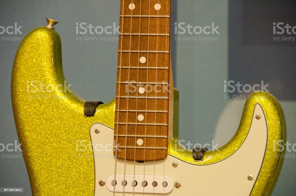Fragments of  neon yellow electric guitar with blue background stock photo