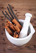 Fragrant cinnamon and vanilla sticks in mortar on rustic board