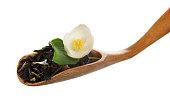 Fragrant tea leaves with cornflower, jasmine flower in spoon isolated.