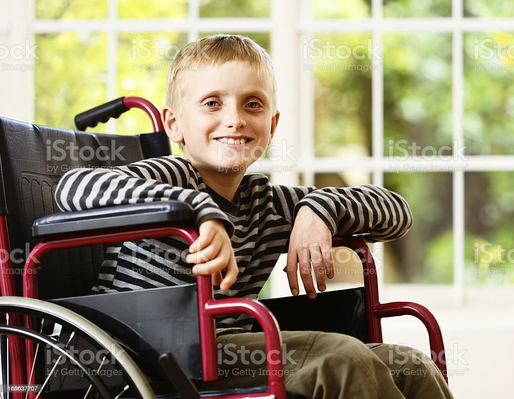 Frail little boy in wheelchair smiles bravely and optimistically stock photo