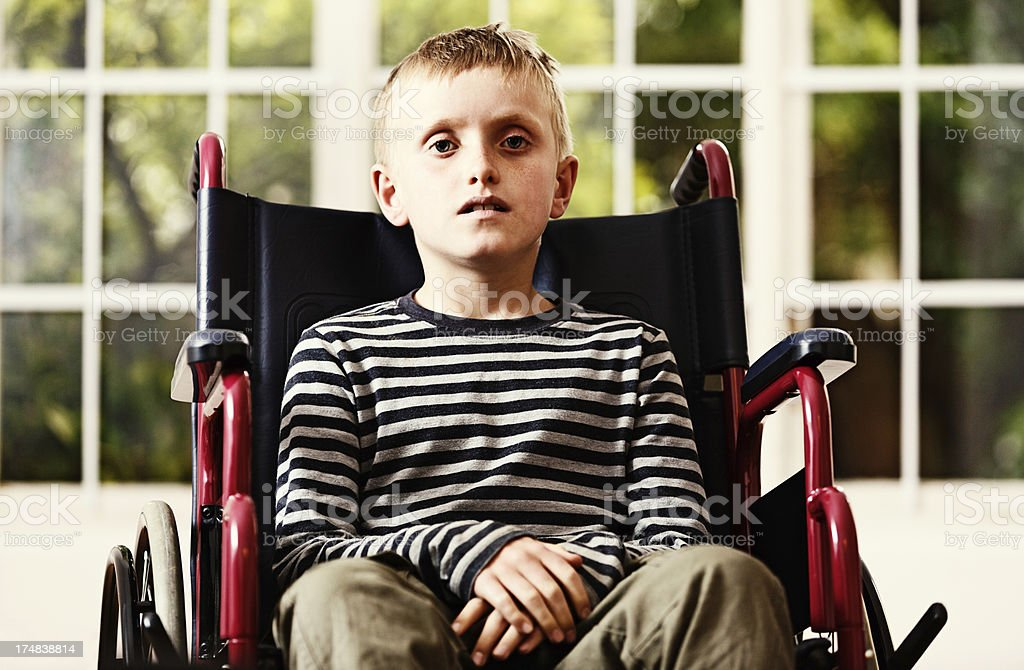 Frail little boy sitting in wheelchair looks worried stock photo