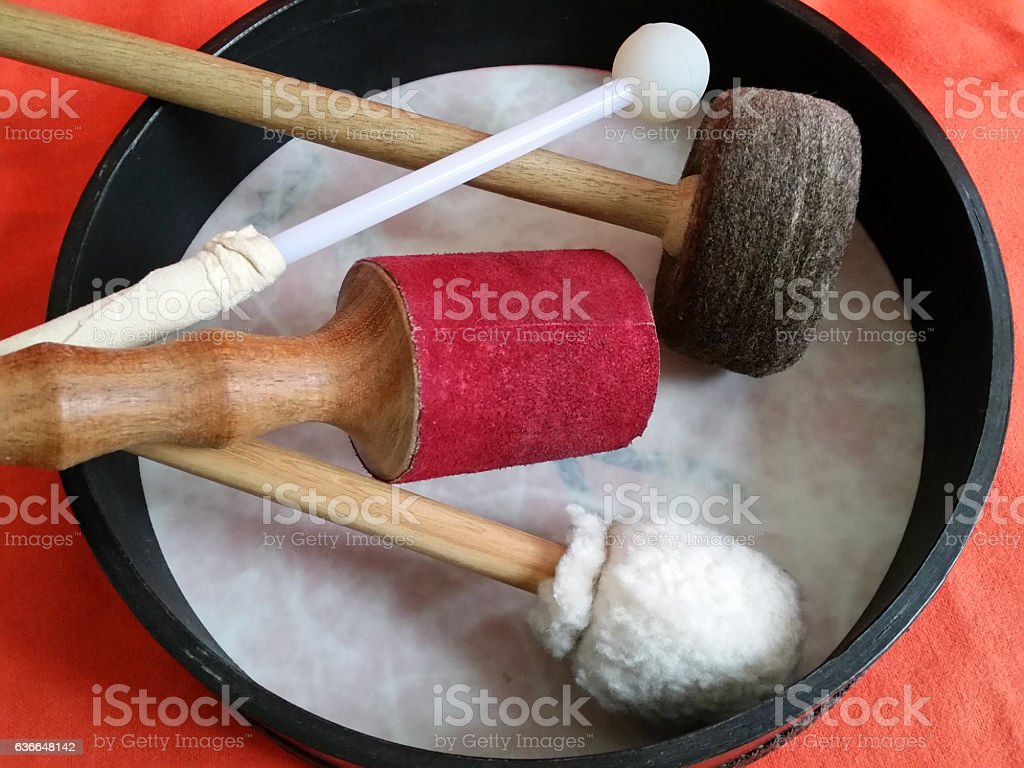 Frame drum with four different drum mallets or drumsticks stock photo