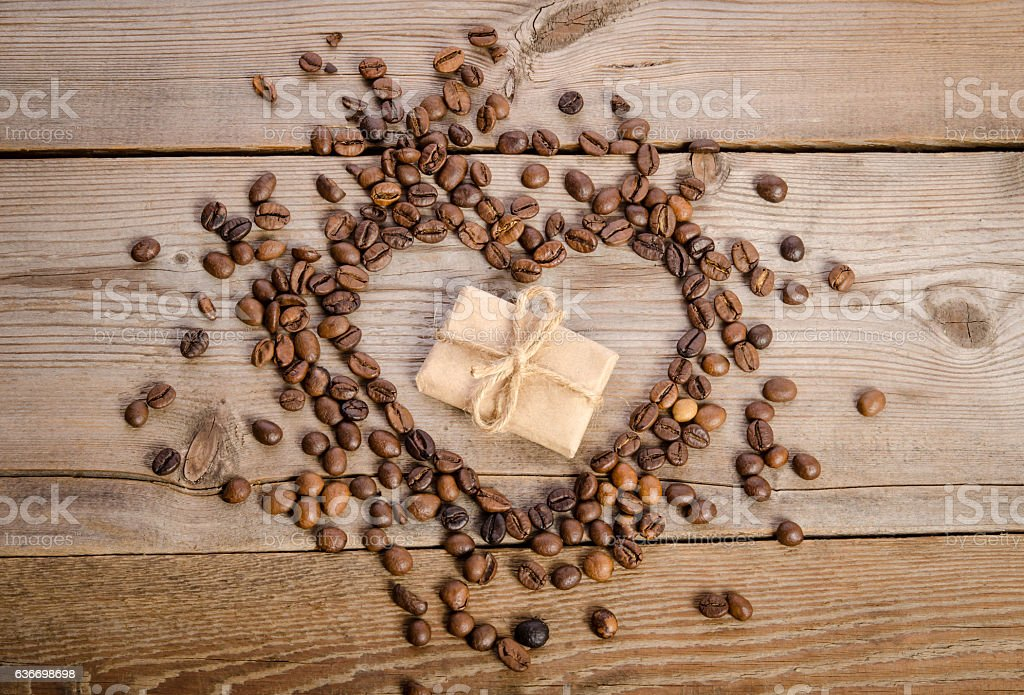 Frame- heart from coffee beans and small parcel inside it stock photo