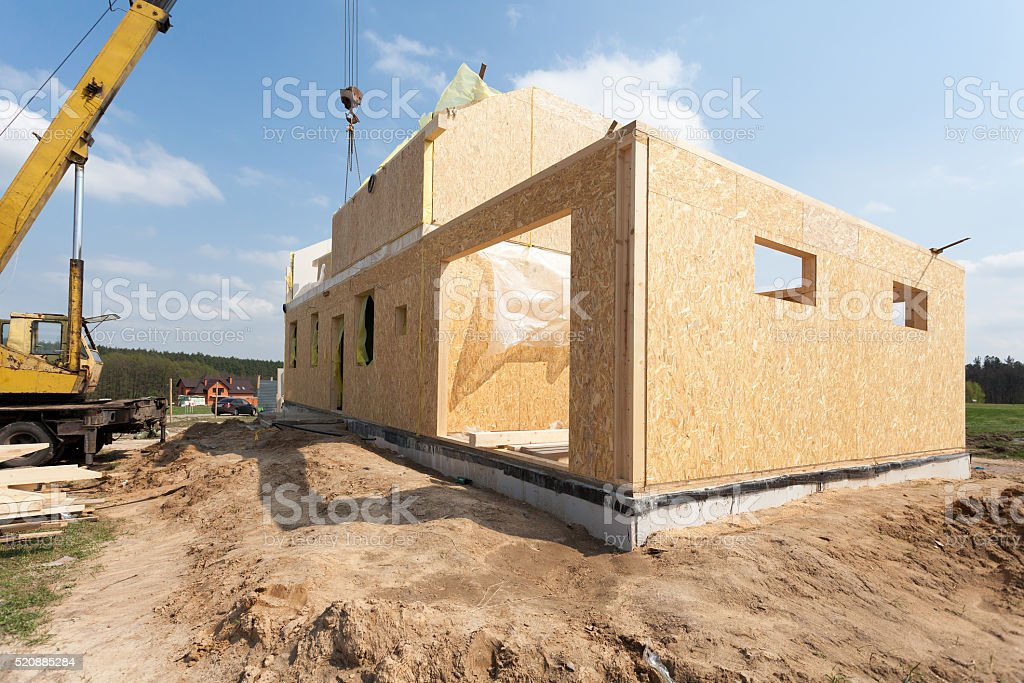 Frame house construction. View on new building with crane stock photo