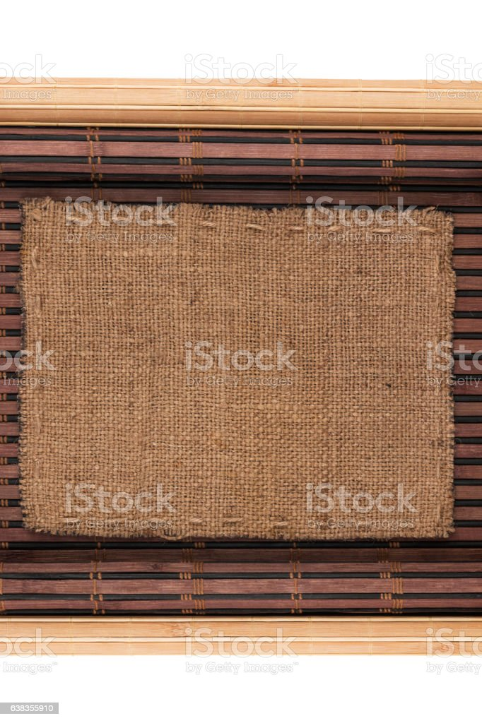 Frame made of burlap lying on a bamboo mat in stock photo