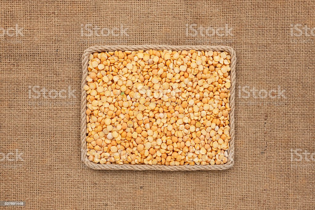 Frame made of rope with pea grains on sackcloth stock photo