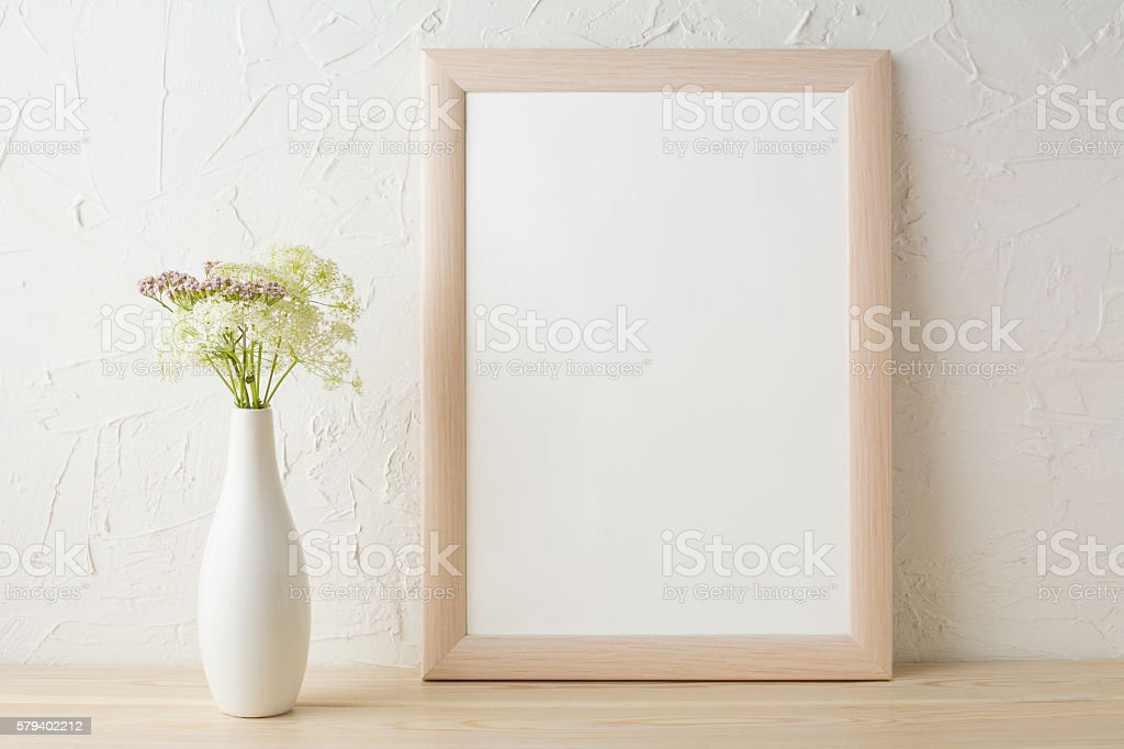 Frame mockup with tender flowers in white stylish vase. Poster white...