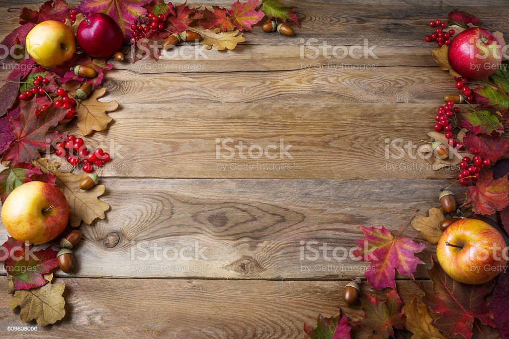 Frame of apples, acorns, berries and fall leaves, wooden background stock photo