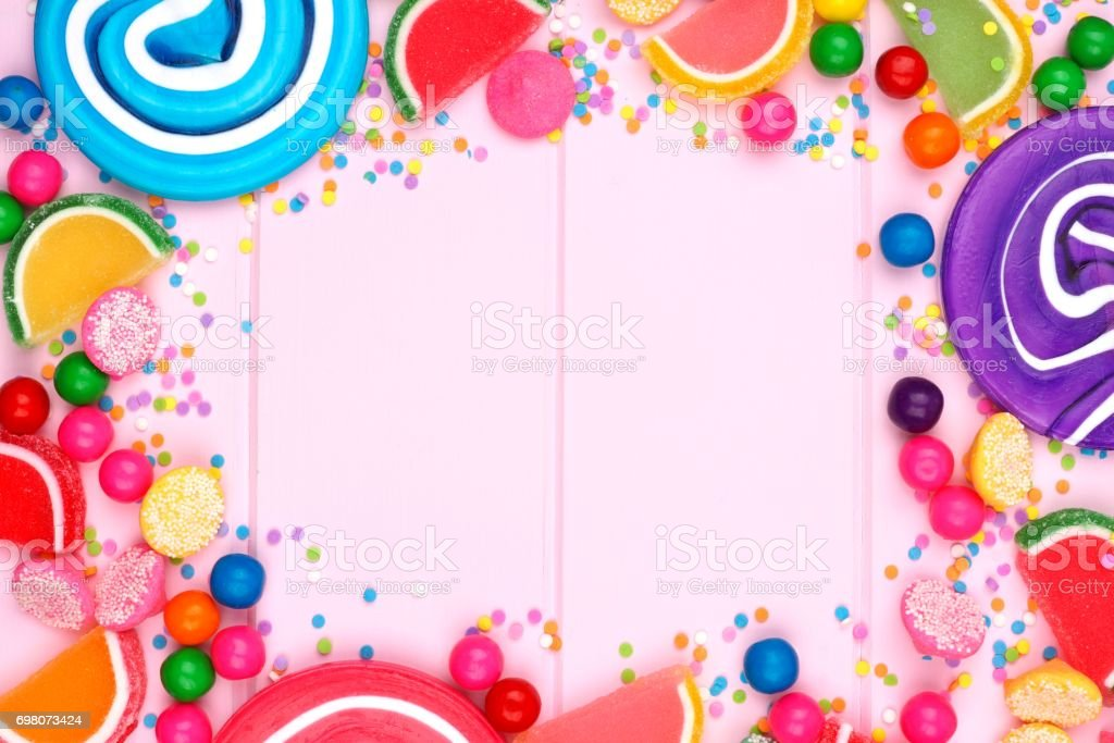 Frame of assorted colorful candies against pink wood stock photo