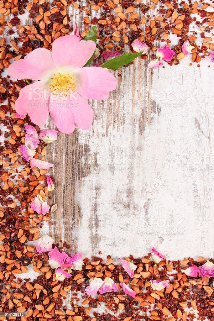 Frame of dried wild rose petals, fresh flower, tea grains stock photo