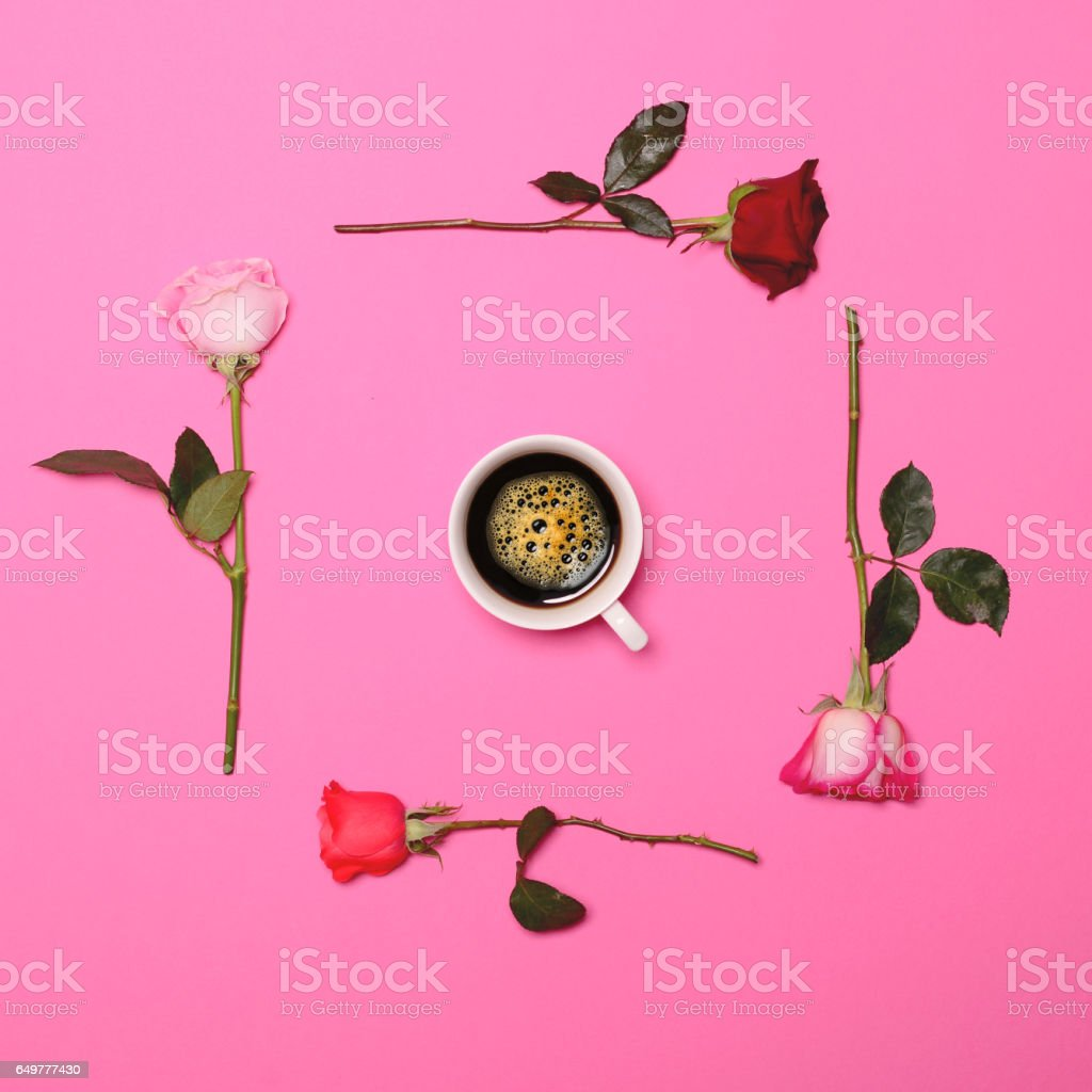 Frame of fresh colorful roses on pastel pink background with perfect coffee cup in middle - Flat lay stock photo