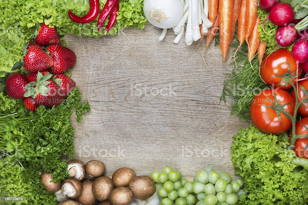 Frame of fresh fruits and vegetables on cutting board royalty-free stock photo