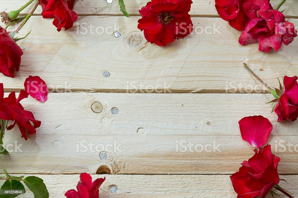 Frame of red roses on wooden background stock photo
