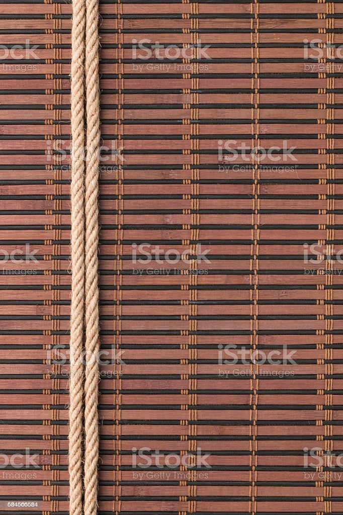 Frame of two smooth ropes lying on a bamboo mat stock photo