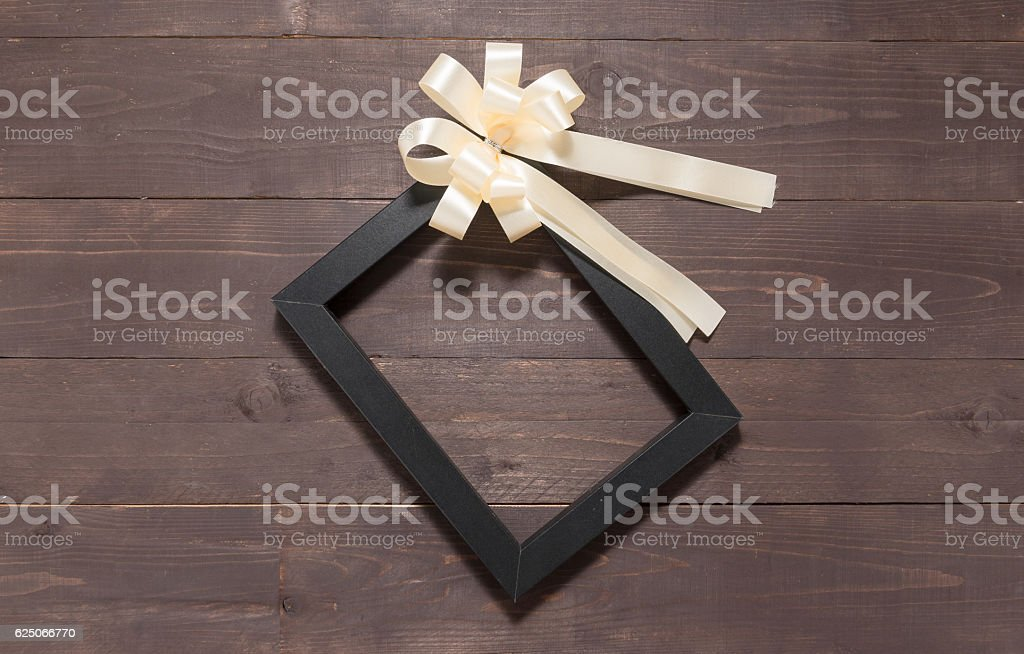 Frame picture and white ribbon are on wooden background stock photo