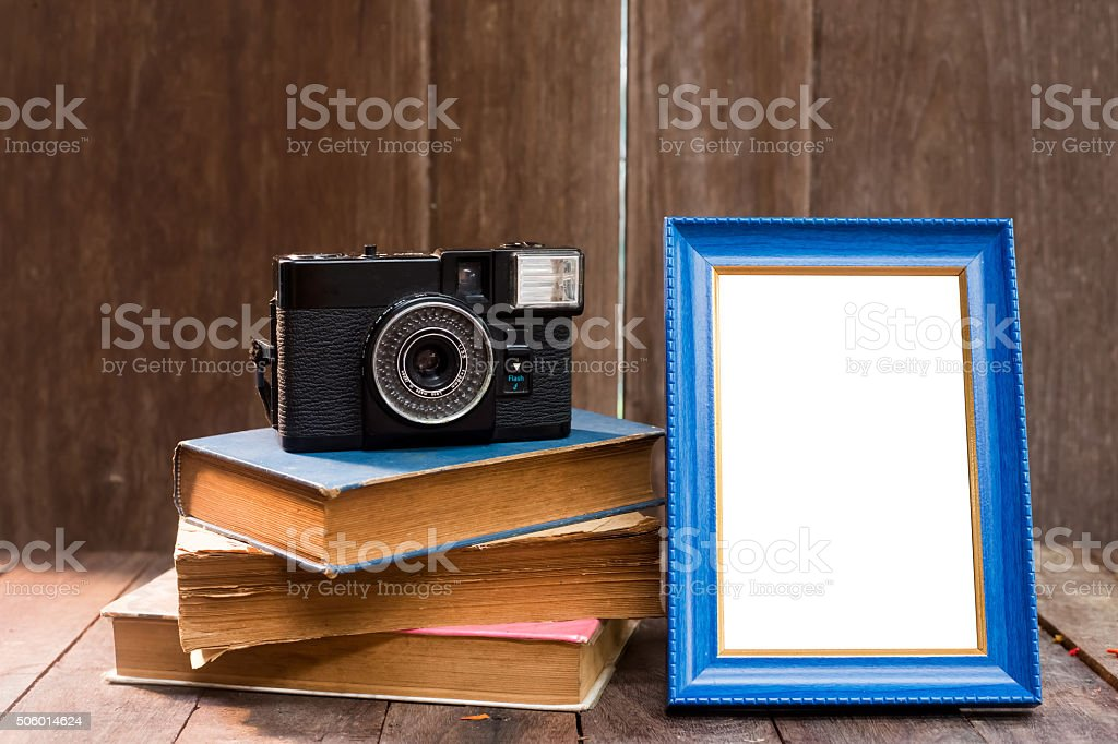 Frame with old books and old camera on wood table stock photo