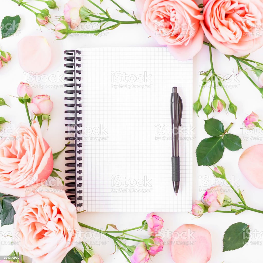 Frame with pink roses, paper notebook and pen on white background. Flat lay, top view. Workspace background. stock photo