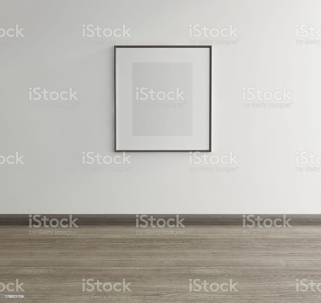 Framed art of gray rectangle hanging above gray wood floor royalty-free stock photo