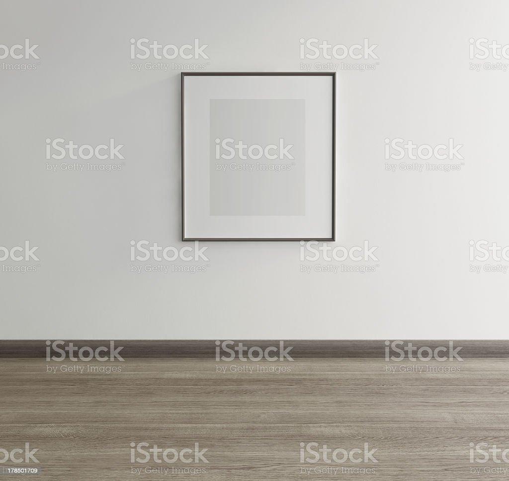 Framed art of gray rectangle hanging above gray wood floor stock photo
