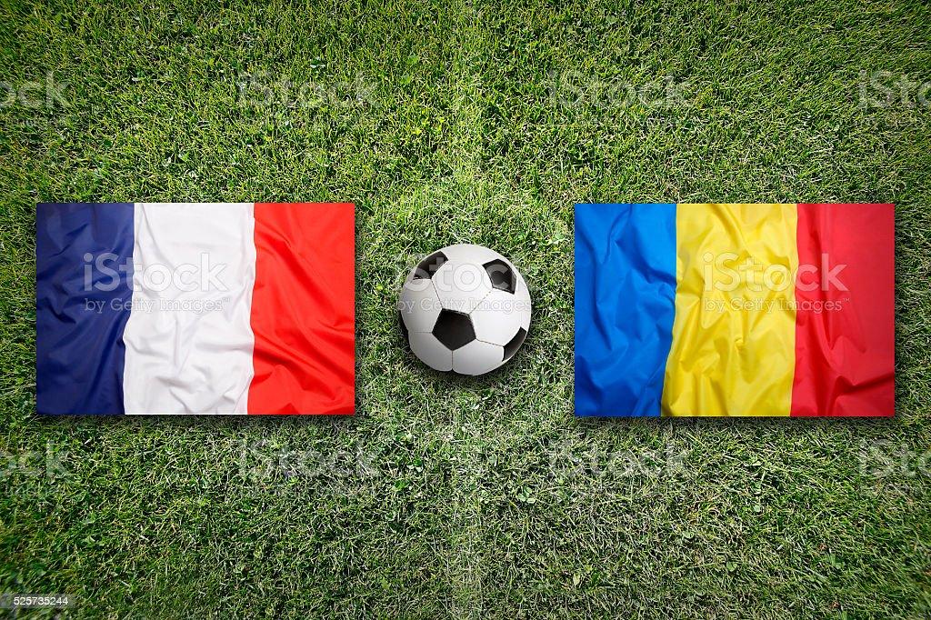 France vs. Romania flags on soccer field stock photo