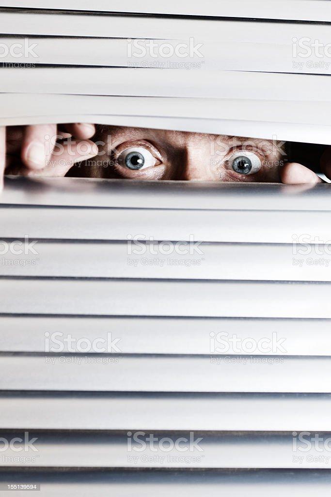 Frantic looking man's eyes peep through blinds at something terrifying stock photo