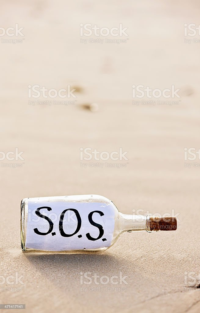 Frantic SOS message in bottle on deserted beach stock photo