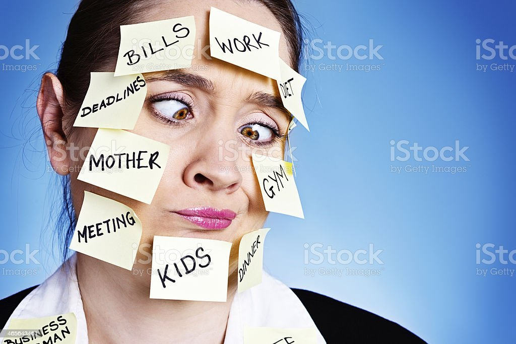 Frantic woman squinting at task reminders: too much multitasking! royalty-free stock photo