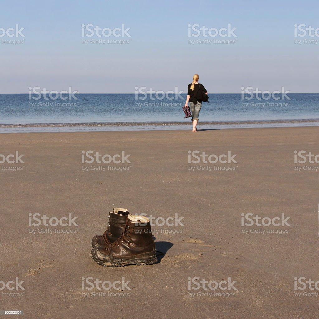 Frau am Strand und zurück gelassene Wanderschuhe auf Helgoland Düne royalty-free stock photo