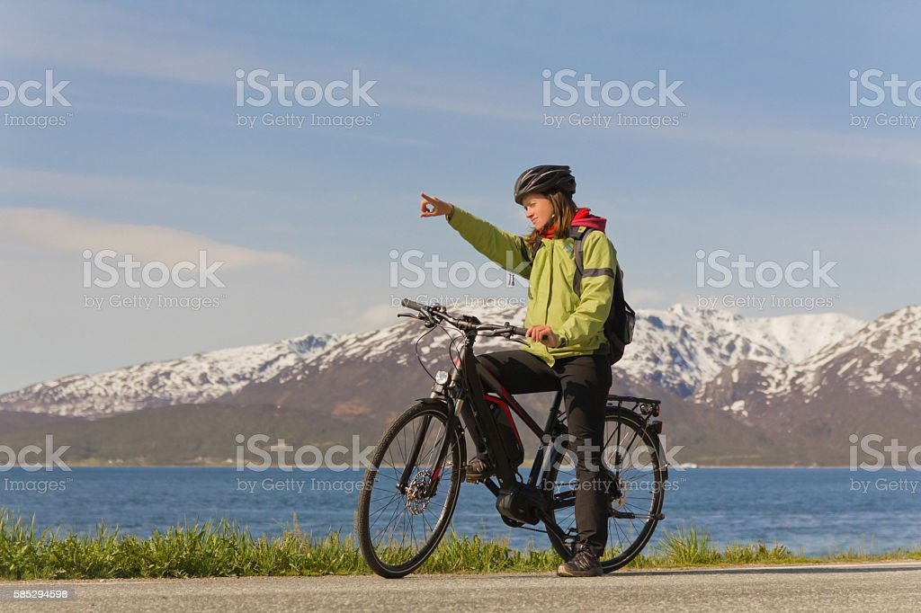 Frau auf Fahrrad/E-Bike zeigt Weg - vor Berg Kulisse stock photo