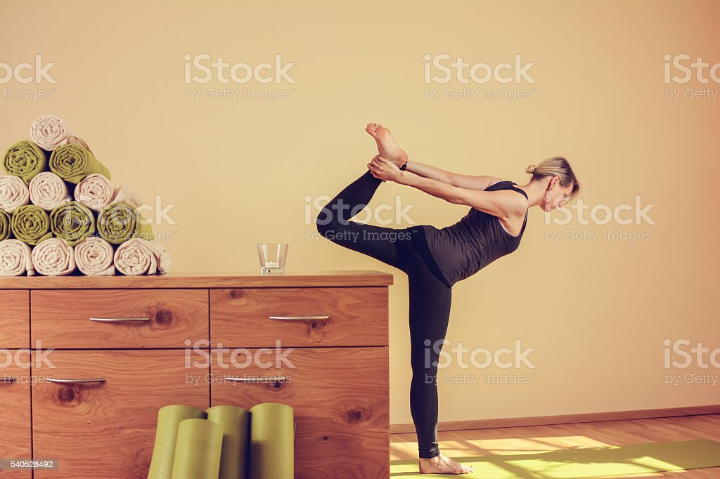 Frau die Yoga macht davor ein Kasten mit handtücher stock photo