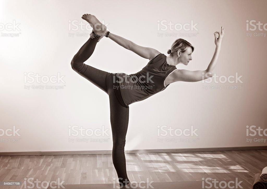 Frau die Yoga macht im stehen auf Yogamatte stock photo