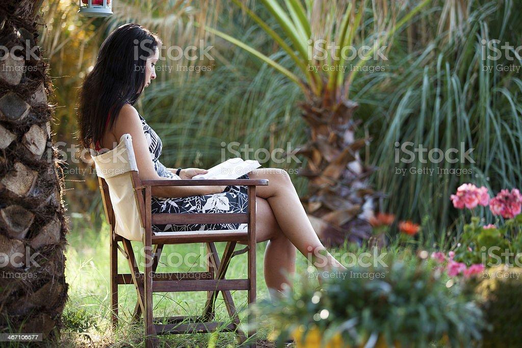 Frau liest entspannt ein Buch im tropischen Garten stock photo
