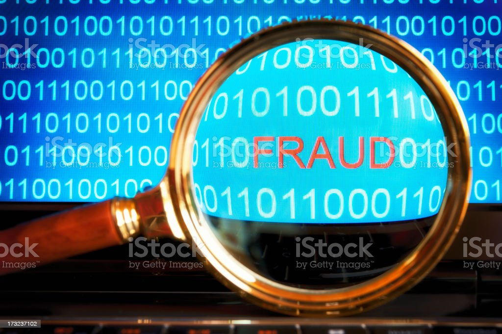 Fraud code revealed through a magnifying glass stock photo