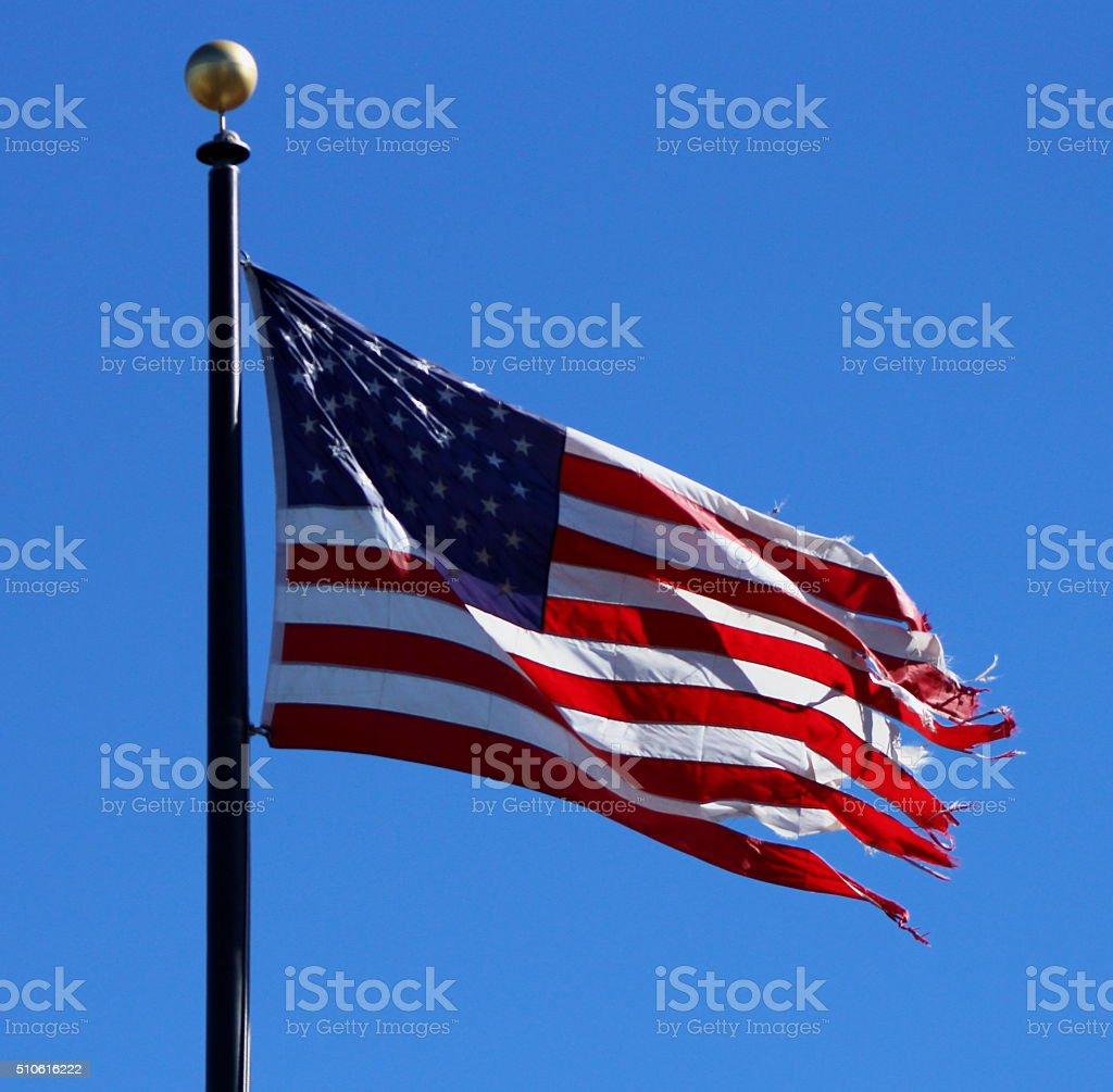 Frayed American Flag Against Blue Sky stock photo