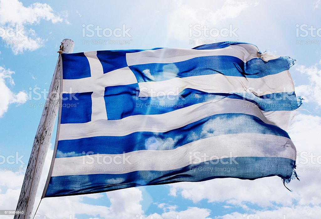 Frayed national flag of Greece blowing in the breeze stock photo