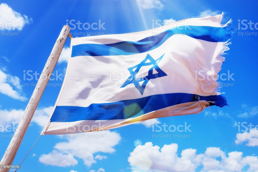 Frayed national flag of Israel flying in the breeze stock photo