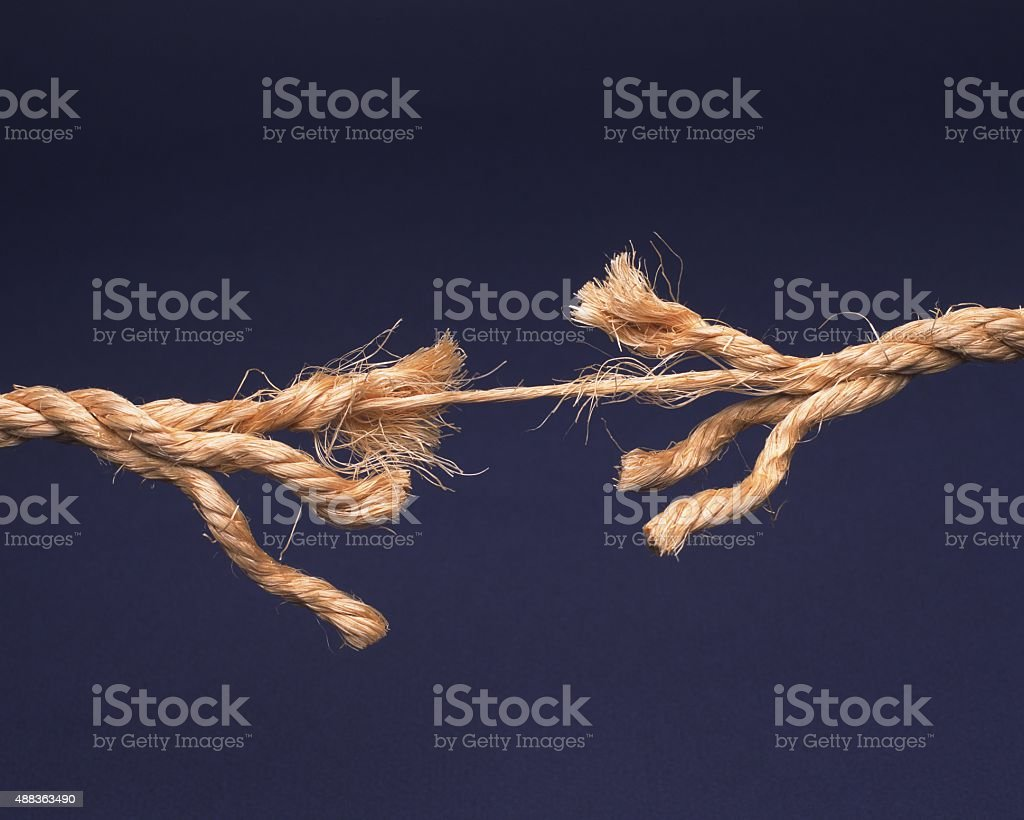Frayed rope about to break isolated on blue background stock photo