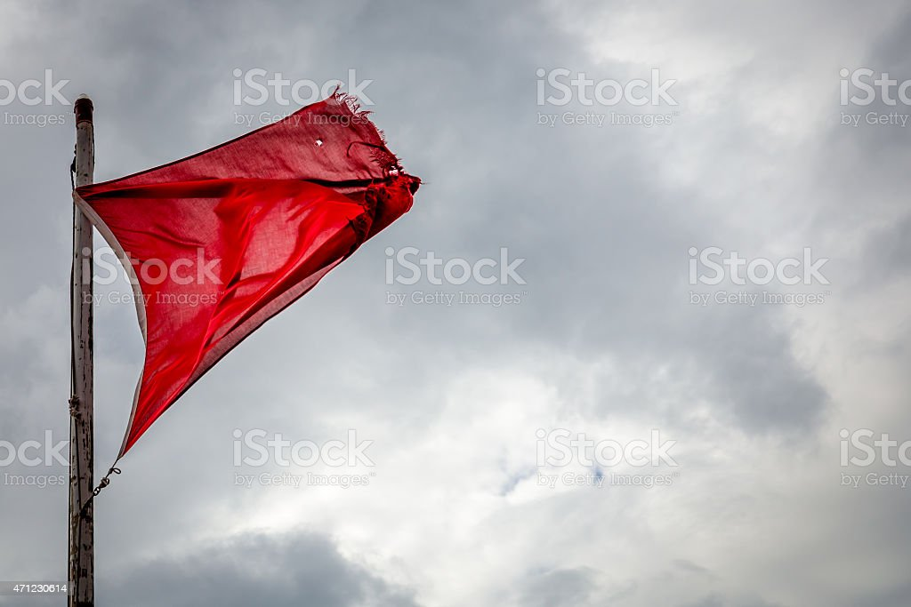 Fraying red flag in harsh wind before a storm stock photo