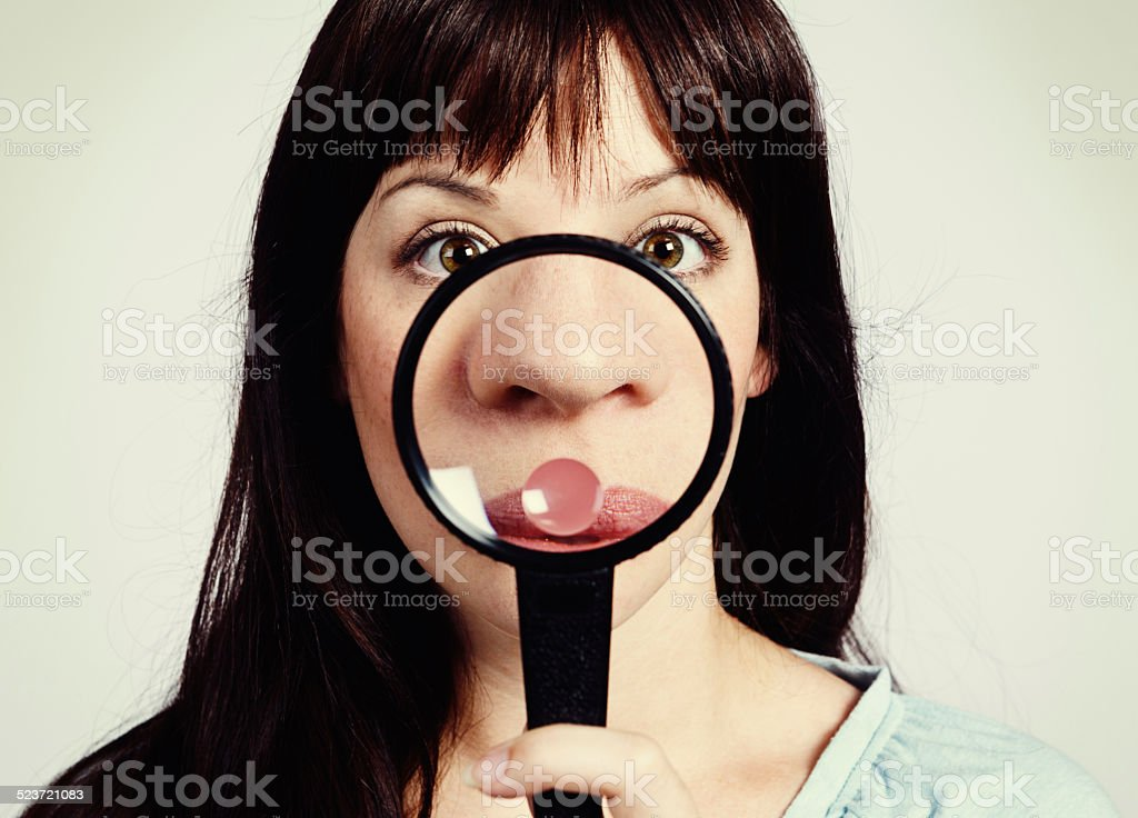 Freckles, oh no! Young beauty examining nose through magnifying glass stock photo