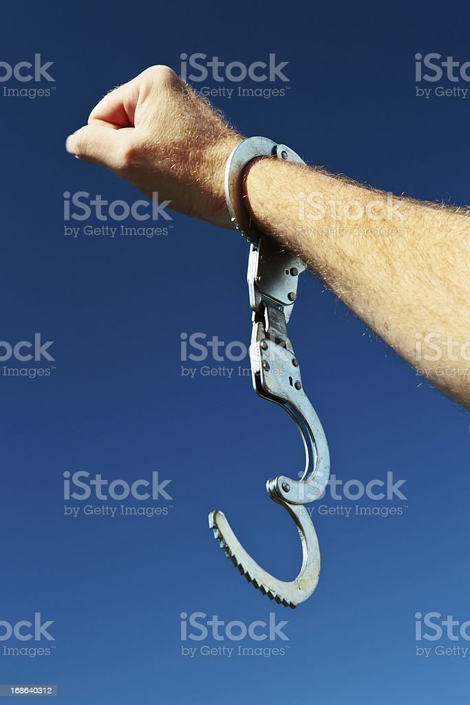 Free at last! Hand with clenched fist and open handcuff royalty-free stock photo