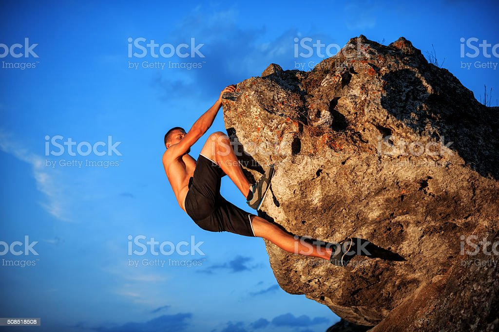 Free climber holding on the cliff stock photo