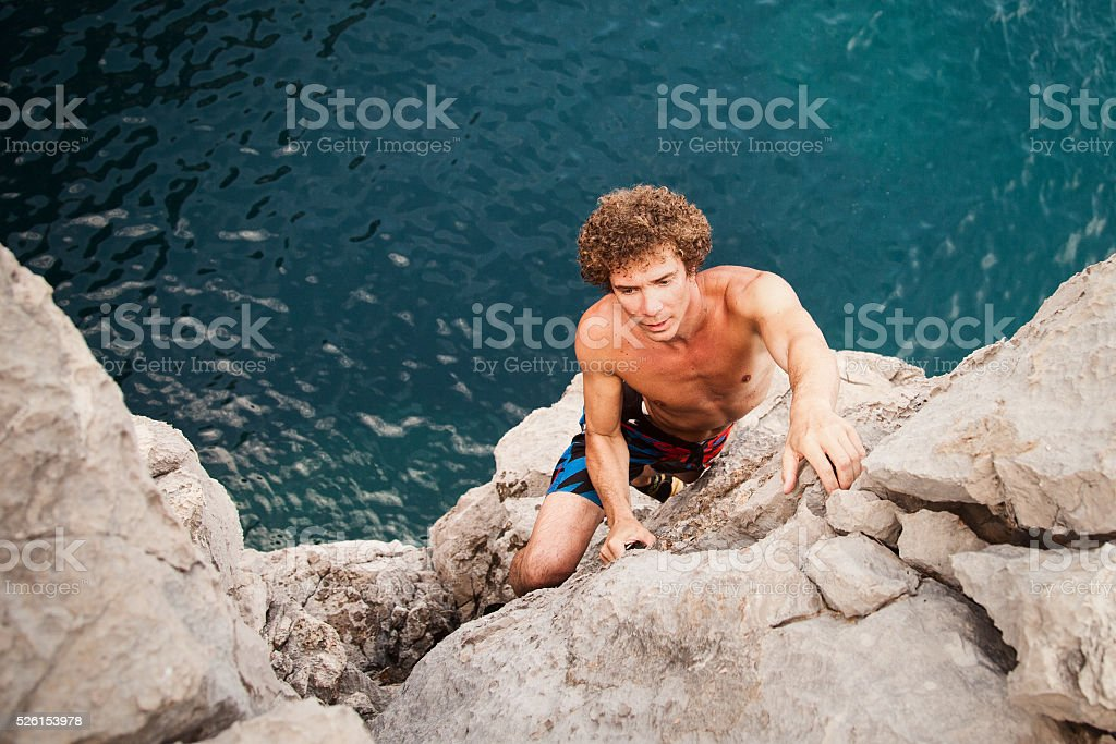 Free climbing on the cliff above the sea stock photo